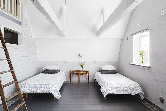 A minimalist white bedroom with two twin beds.