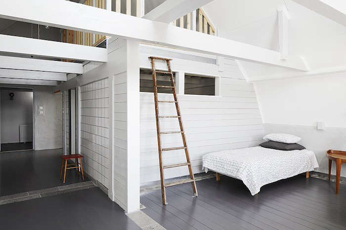 The walls and ceiling of this lofty bedroom are covered in white painted shiplap paneling. (See Expert Advice: The Enduring Appeal of Shiplap.)