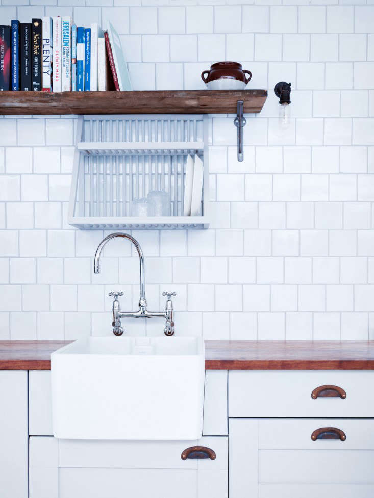 A small plate rack fits perfectly above a narrow utility sink from A Sympathetic Renovation in Stoke Newington, London.