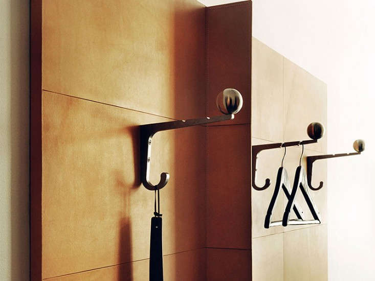 Sculptural brass hooks mounted on wood panels created attractive open storage.