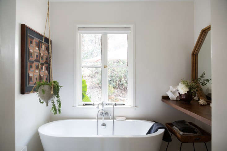 A window removed from the guest room was put to use in the overhauled bathroom. The couple found a bathtub they liked in a showroom and then tracked down the same model online for less. &#8