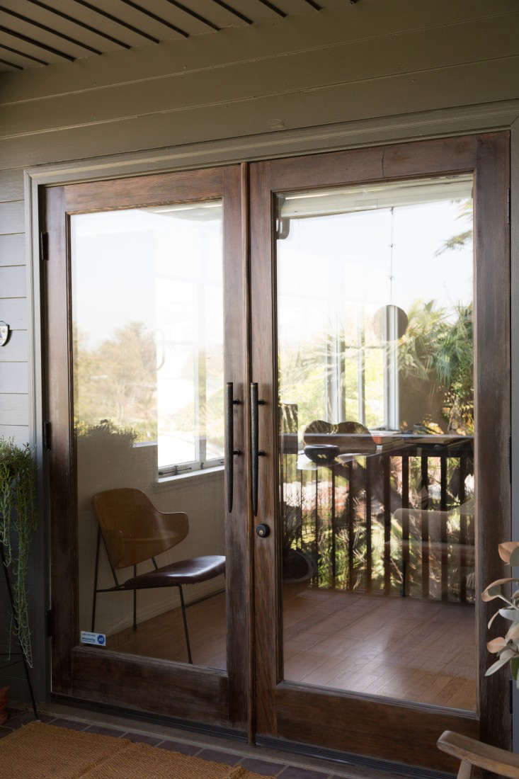 To connect indoors and out, Momo and Alexander installed several sets of French doors, including at the entry, shown here (where they replaced a single wood door). After puzzling over how to afford French doors, they used wood-framed windows, $0 a panel, from Home Depot and stained the wood themselves. A friend at Hot Metal Soup in New York made the front handles.