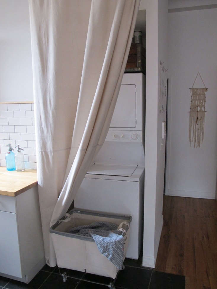 A drop cloth becomes a curtain to conceal the washer/dryer in a small apartment in DIY: The $65 Laundry Closet, Renter's Edition.