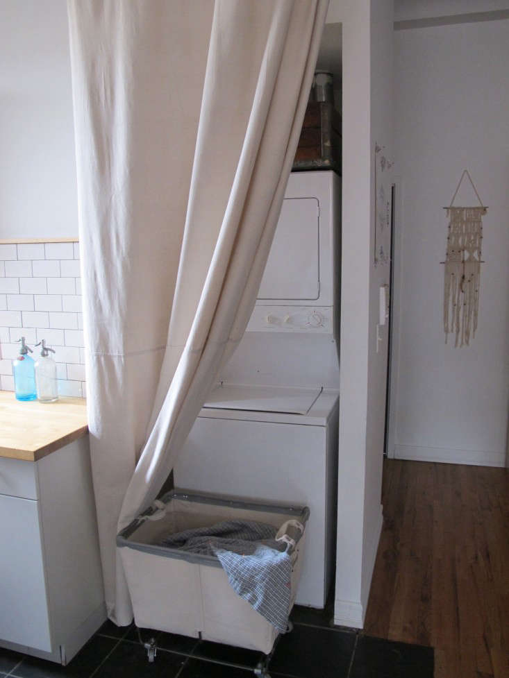 A drop cloth becomes a curtain to conceal the washer/dryer in a small apartment inDIY: The $65 Laundry Closet, Renter's Edition.