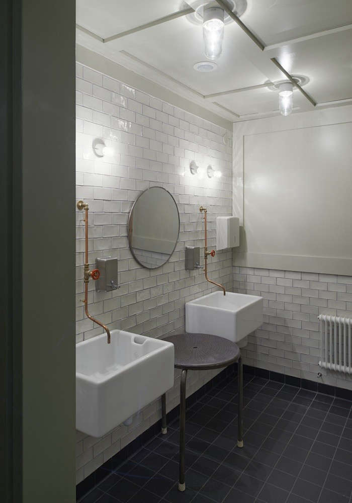The white-and-black-tiled bathroom has an industrial feel. It&#8