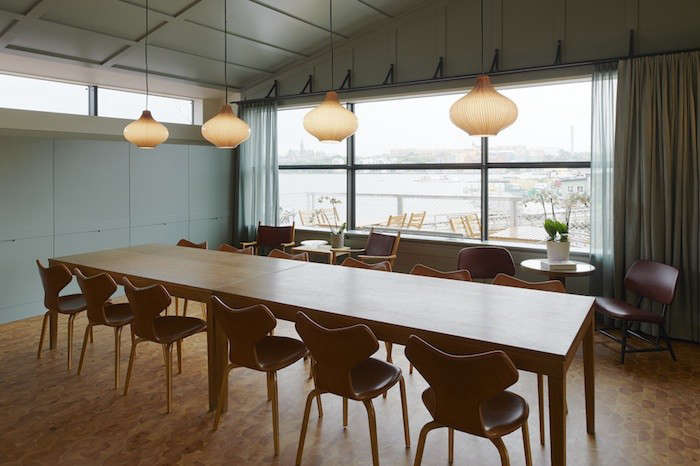 The Club Room, located above the restaurant, offers private events and dinners—and impressive views from a balcony of Saltsjön bay and the island of Beckholmen. The paneled walls and ceiling are painted in a linseed oil and the glass ceiling lamps are by Massimo Vignelli for Venini. The chairs are Arne Jacobsen&#8