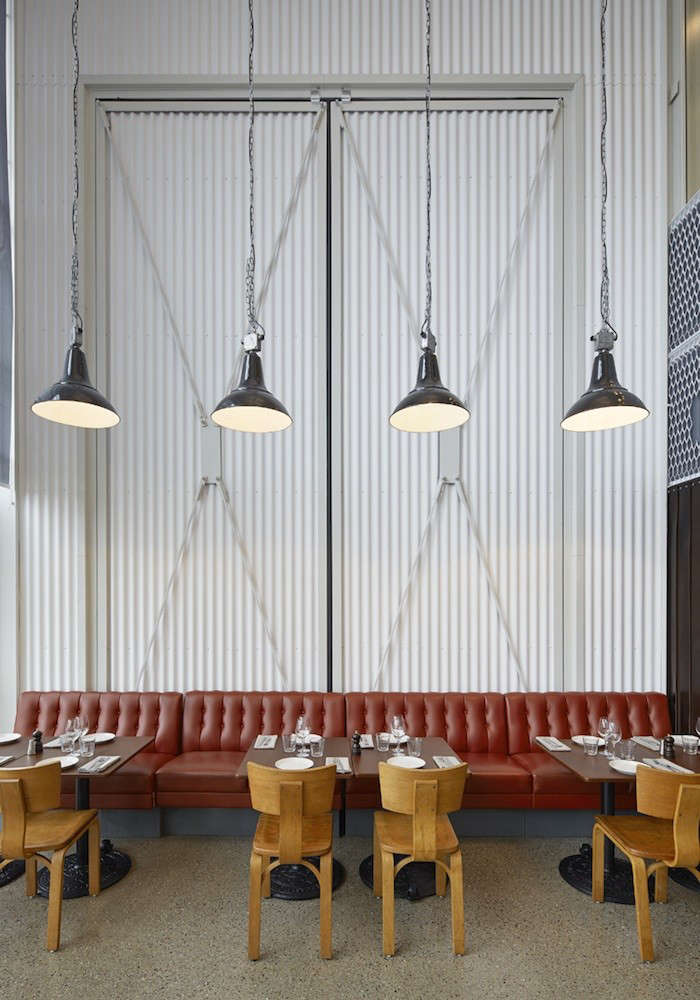 At one end of the Slip, a red leather sofa made for the dining room of a food supply company stands against a white corrugated metal wall. Vintage Thonet bentwood chairs are matched with Roll Tables by Tom Dixon that have cast-iron bases with wheels. The hanging industrial pendant lamps are from the 50s.