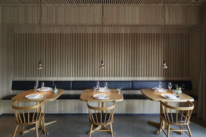The dining room walls and ceiling are covered in slatted oak panels. The built-in sofa is made of oak and leather. Local shipyard carpenters fabricated the custom tables, which are paired with a 50s chair design that&#8