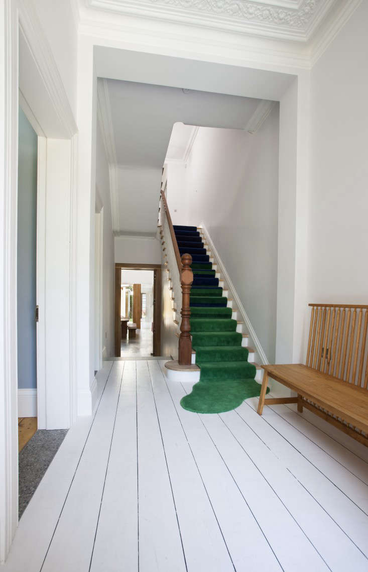 Architect Peter Legge used a green carpet stair runner that spills into a puddle on the floor to soften the entry of the three-story staircase. Photograph by Sean Breithaupt and Yvette Monohan.