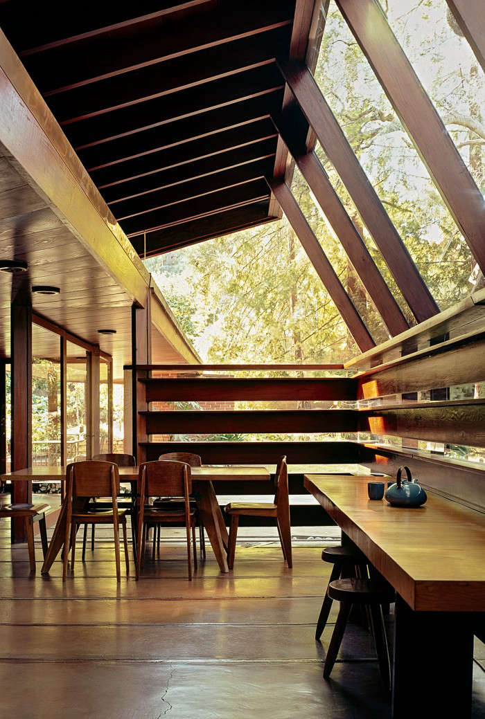 The house is in the Montrose area of Glendale, California, on a heavily wooded site that is visible through the glassed-in ceiling of the dining room. The vintage dining table and chairs are Jean Prouvé designs, and the wood stools are by Charlotte Perriand.