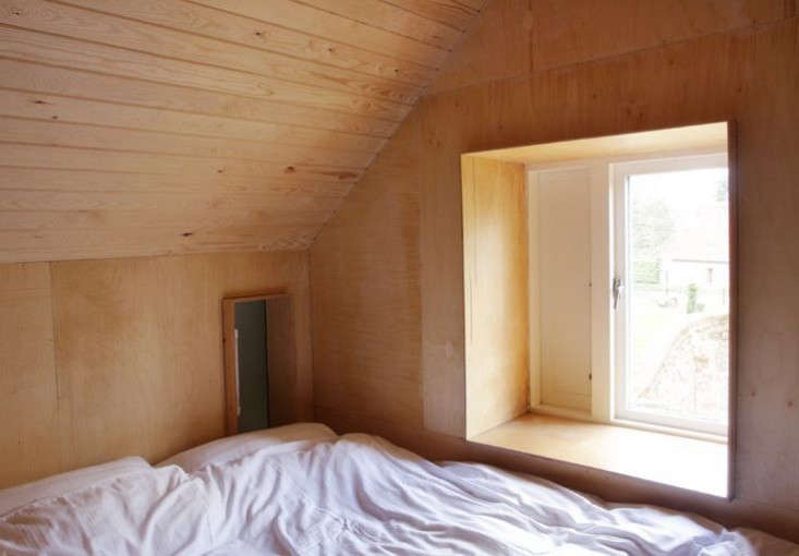 The window has a deep plywood frame that serves as a bedside ledge. The small hatch overlooks downstairs.