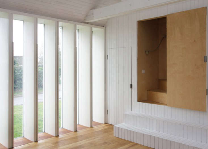 The designers opened the room to the outdoors by inserting a floor-to-ceiling slatted window (with concealed shutters that close for privacy).