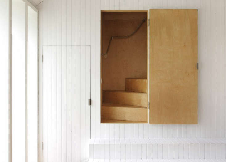Two exterior steps—of hinged tongue-and-groove-boarding that double as storage—connect to a concealed stairway of birch plywood.