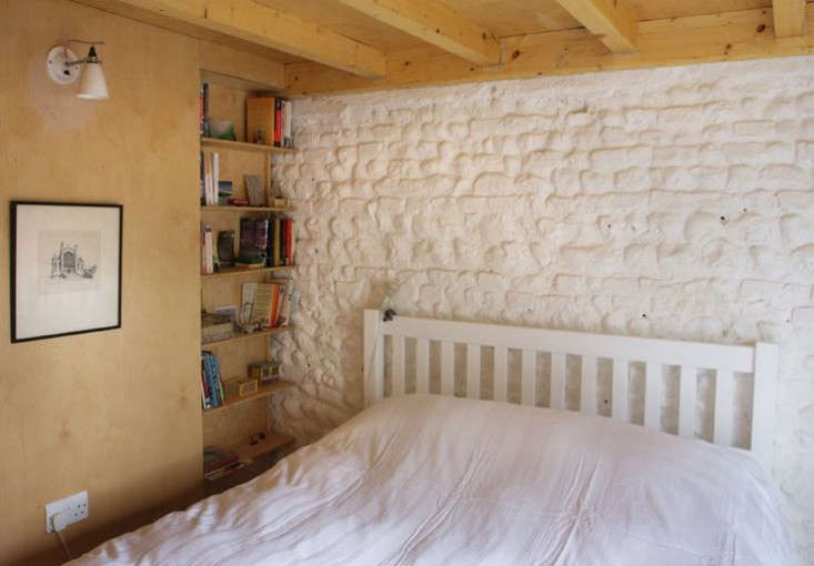 The first floor bedroom has inset birch ply shelving and exposed rafters. The wall light is Original BTC&#8