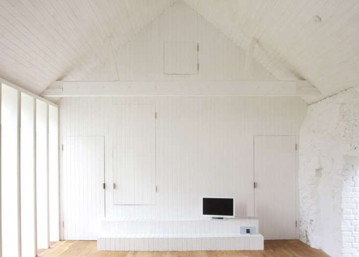 To keep the barn-like quality of the interior, the architects introduced an ingenious wall of tongue-and-groove paneling detailed with hidden doors and cupboards. &#8