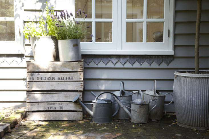 a collection of wooden crates and watering cans add a rustic vibe to the urban  15