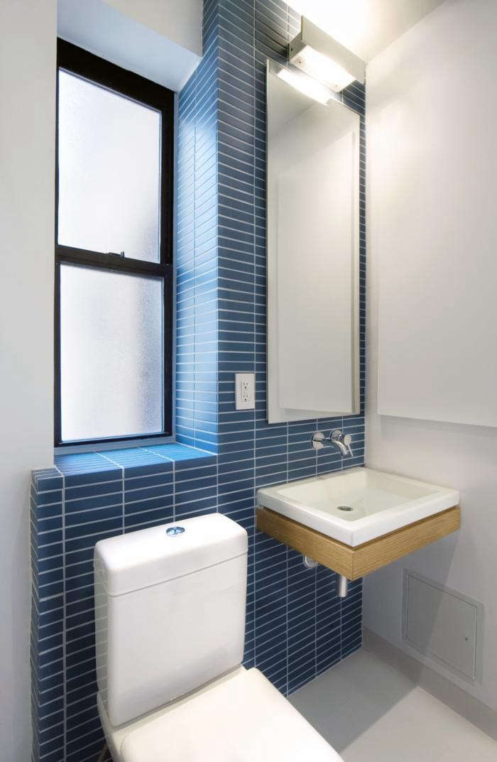 In this small New York bathroom by Uniform Design, one light fixture performs double duty: It shines into the mirror and up-lights onto the white ceiling for enhanced reflection. Uniform Design are experts in the design of small bathrooms; have a look at their work in our postThe Architect Is In: Instant Affordable Bathroom Design.