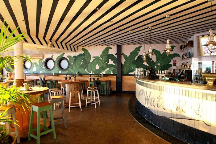 the bar area features a rounded wooden bar and a wall mural of green palm leave 10