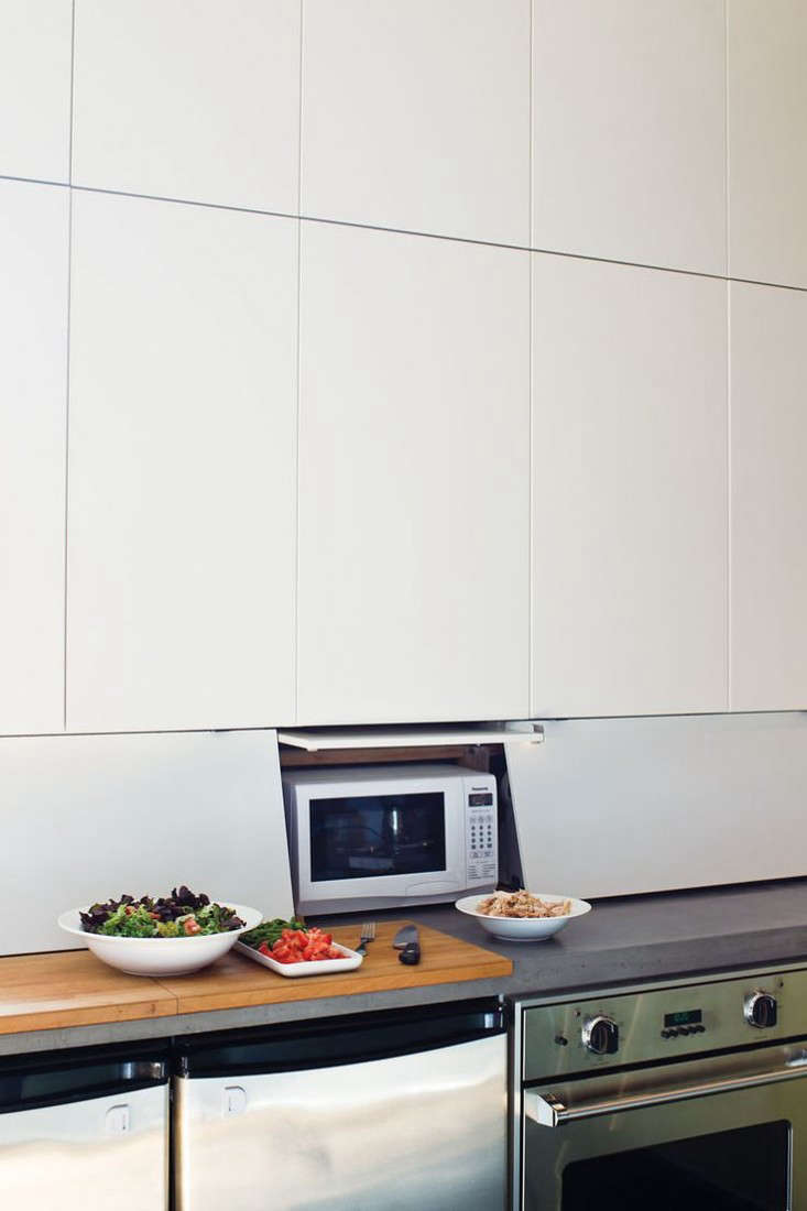 Ikea cabinets with swing-up doors for countertop appliances. Photograph courtesy ofDwell.