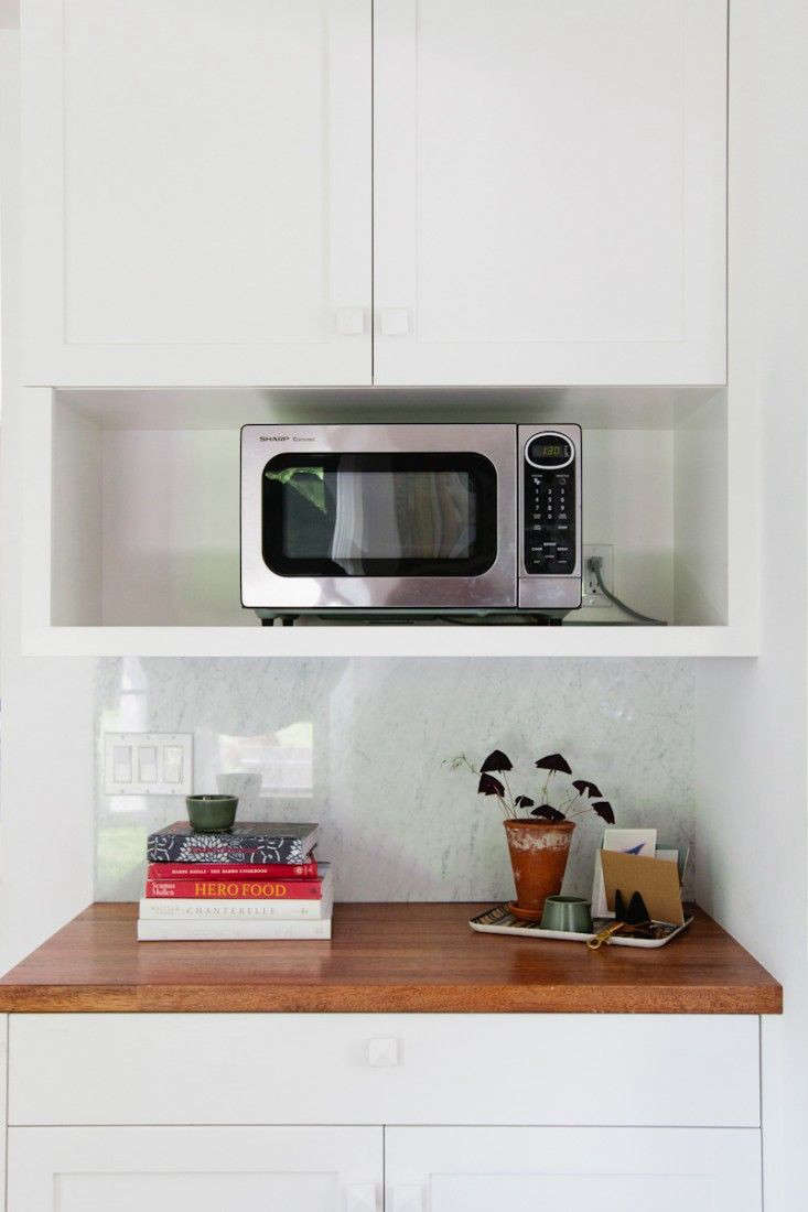 Barbara Bestor tucked a microwave in a side cabinet in A New England Kitchen by Way of LA.