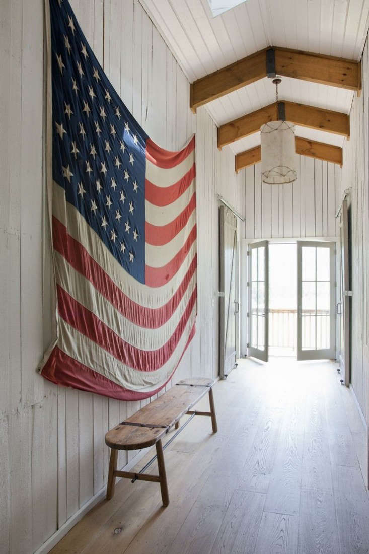 A large old American flag hangs in the hallway of a white painted barn. Photograph fromRachel Halvorson Designs.