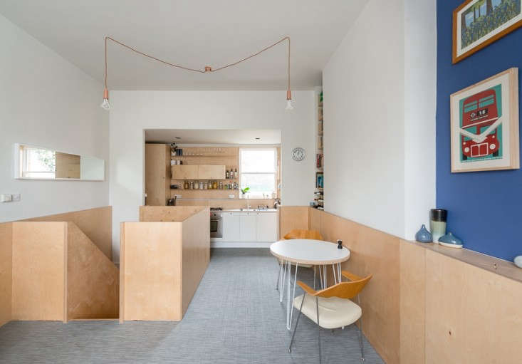A plywood chair rail wraps around the kitchen and dining rooms in A Compact Apartment in London by a Craft-Oriented Architect.