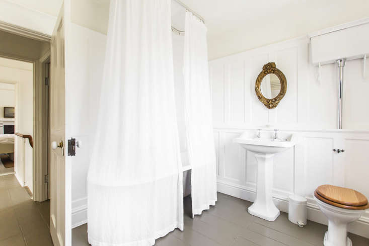 in the lone bathroom, a floor to ceiling white shower curtain envelops a cast i 19