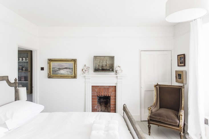 In an elegantly furnishedKid & CoeSeaside Rental in Cornwall, England, the bedrooms are all cloaked in white, and this one has its own brick fireplace.