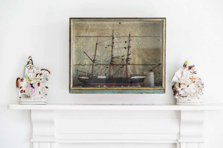 above the fireplace mantel, an oil painting of a tall ship is flanked by staffo 17
