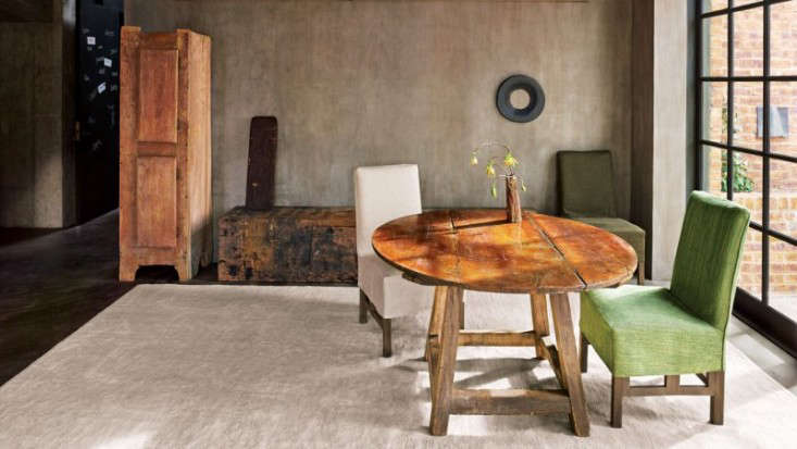 Vervoordt is adept at mixing primitive elements (a rough-hewn table) with luxe pieces (a green velvet chair).