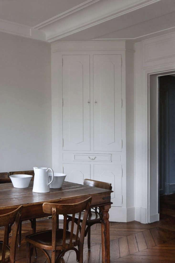 In An Artfully Appointed Parisian Flat, available for rent: an original corner cupboard and herringbone floors. Photography by Paul Raeside, courtesy of Behomm.