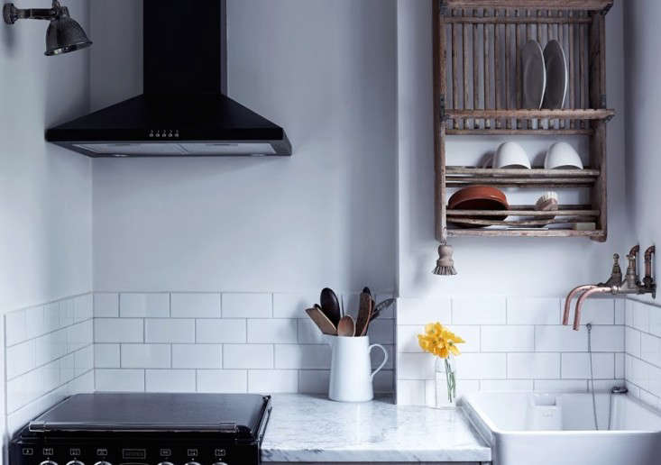 A wall-mounted vintage plate rack in a Primrose Hill kitchen by Mark Lewis Interior Design in London. Photograph courtesy of Rory Gardiner.