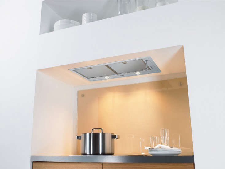 A Miele stainless steel Extractor Unitwith dimmable halogen lights is neatly incorporated in a shelf over a cooktop. Its price, $loading=