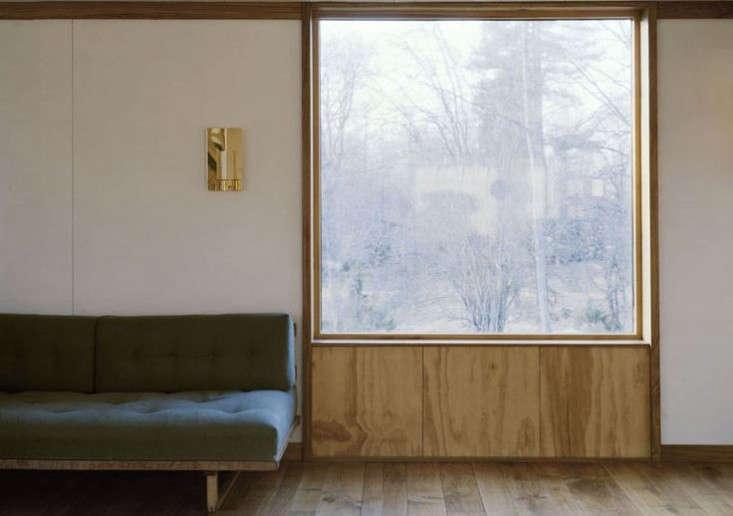 plywood frames a window in a bare bones summerhouse. seescandinavian simplici 24