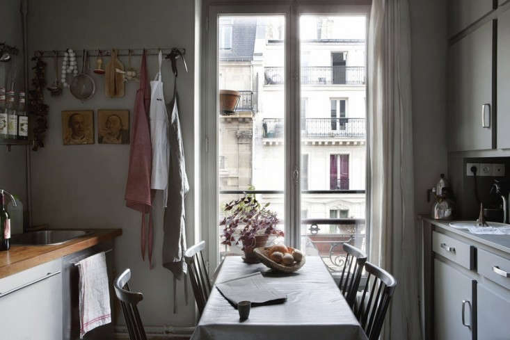 A dining table in a quiet, gray-toned kitchen looks out at Parisian facades. For more, see Cultural Exchange: An Artfully Appointed Parisian Flat. Photography by Paul Raeside, courtesy of Behomm.