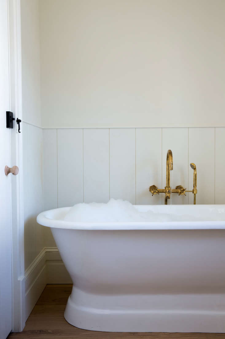 Expert Advice 9 HardWearing Natural Material Recommendations from a Hotelier rivertown lodge bathroom with Waterworks raw brass fixture.