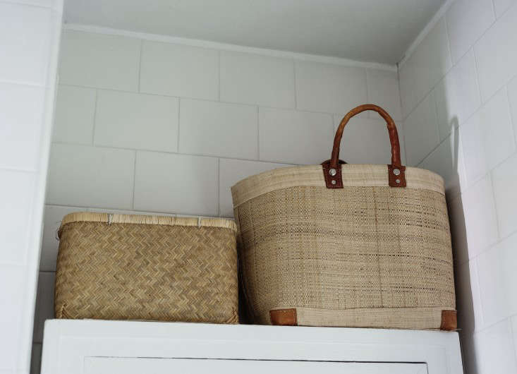 Straw baskets above the cabinet make up for lack of deep shelves. They look tidy because none of their contents peek over the edge.