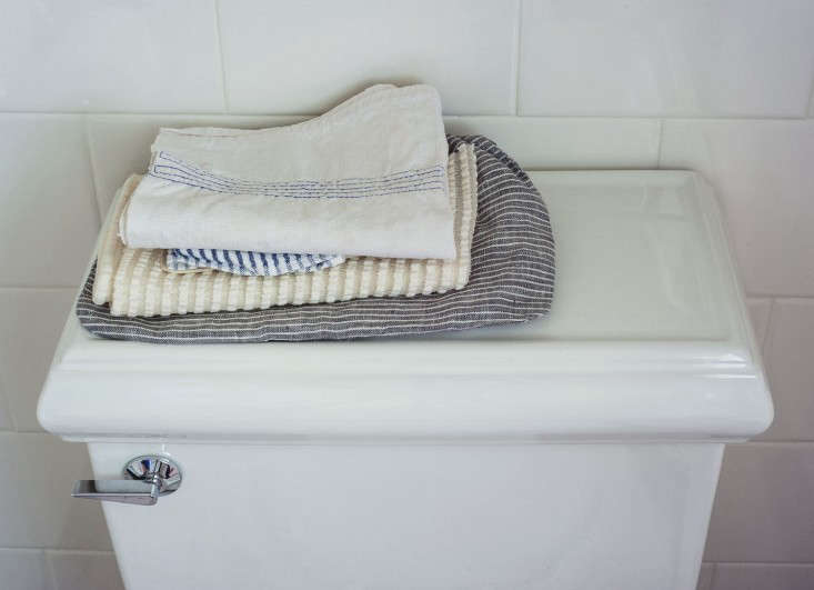 A stack of washcloths sits on the toilet.