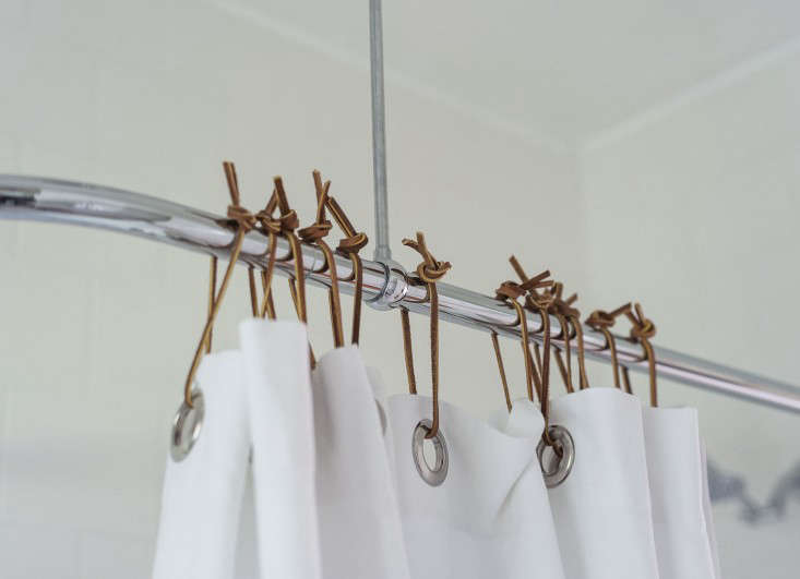 Our shower curtain hangs from homemade rings.