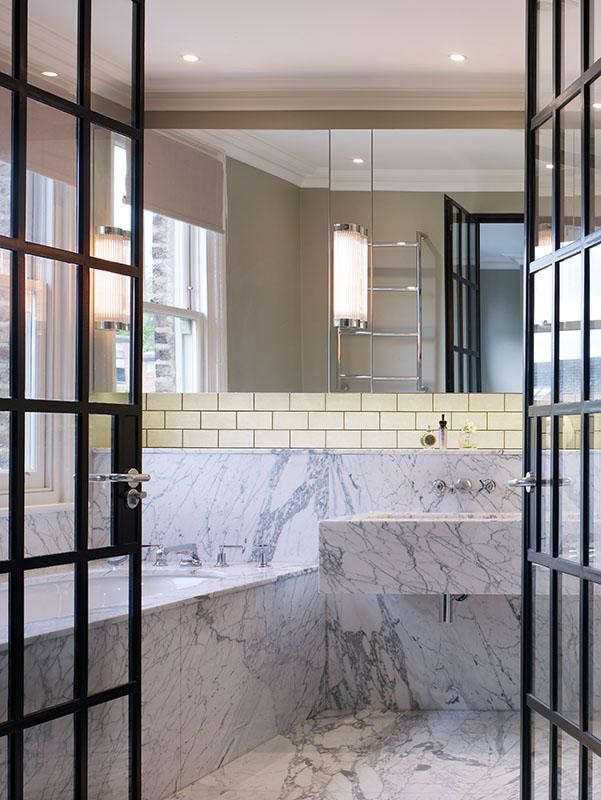 A luxe bath designed by Stiff + Trevillion of London features Arabascato marble and industrial, steel-framed French doors. Photograph by Kilian O&#8