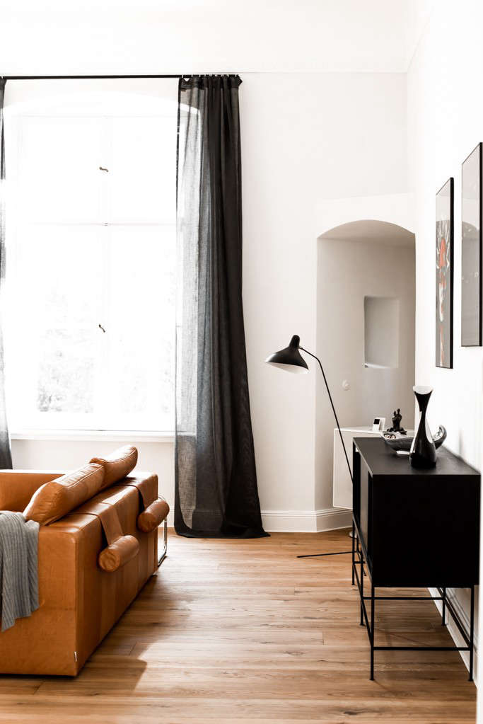 Charcoal curtains are saved from being too severe thanks to sheer linen; all curtains in A Sexy, Minimalist Remodel in Berlin were hand-sewn in Poland.