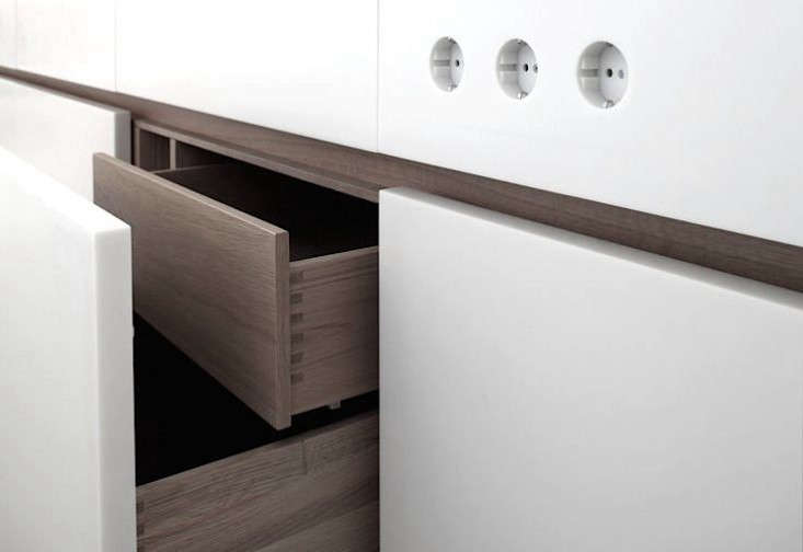 In a fitted kitchen by German company Holzrausch, two-tiered drawers double the storage space (also note the electrical outlets embedded in the Corian countertop).