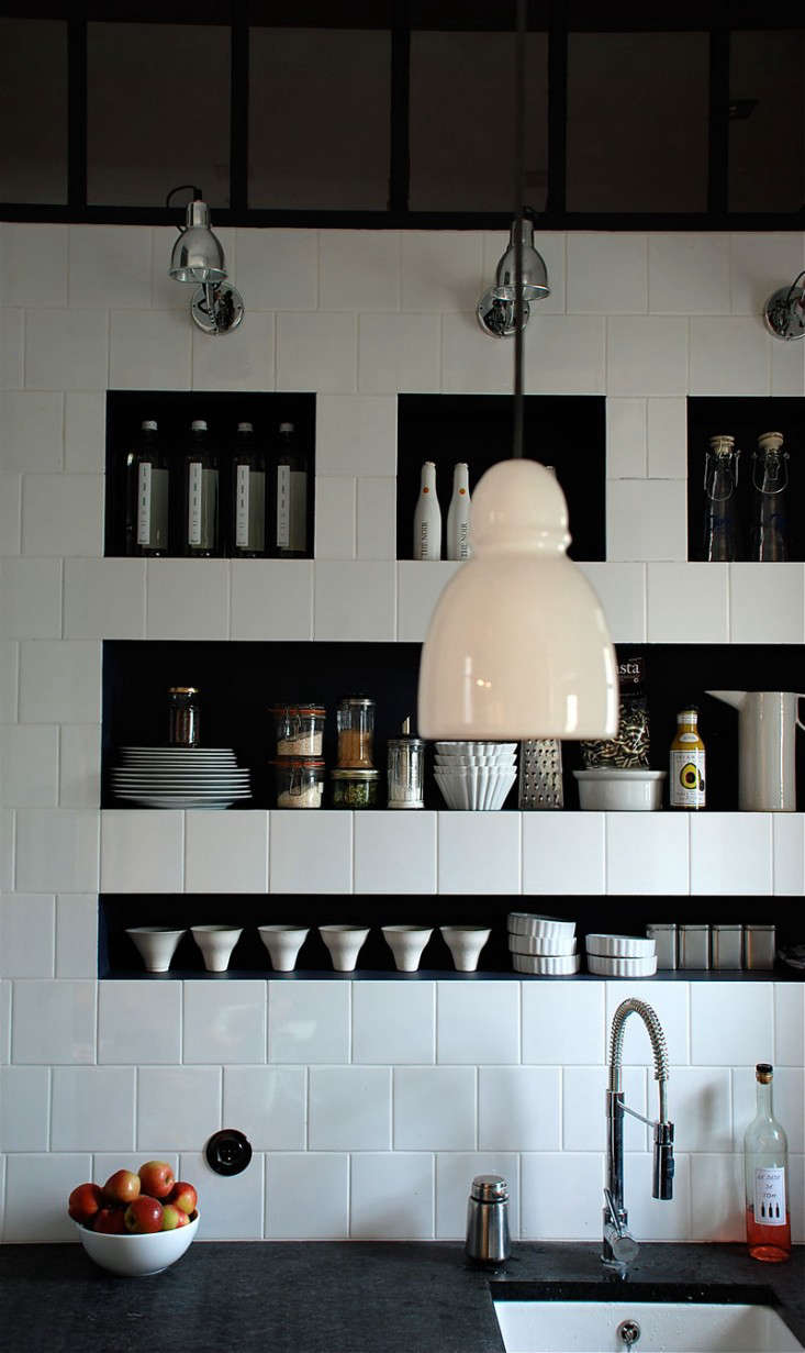 A tiled wall with inset shelving painted black from French designer Marianne Evennou.
