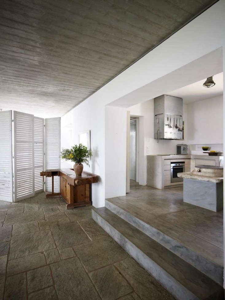 The kitchen steps down to the dining area and living room. The floor is made of stone from Pelion, &#8