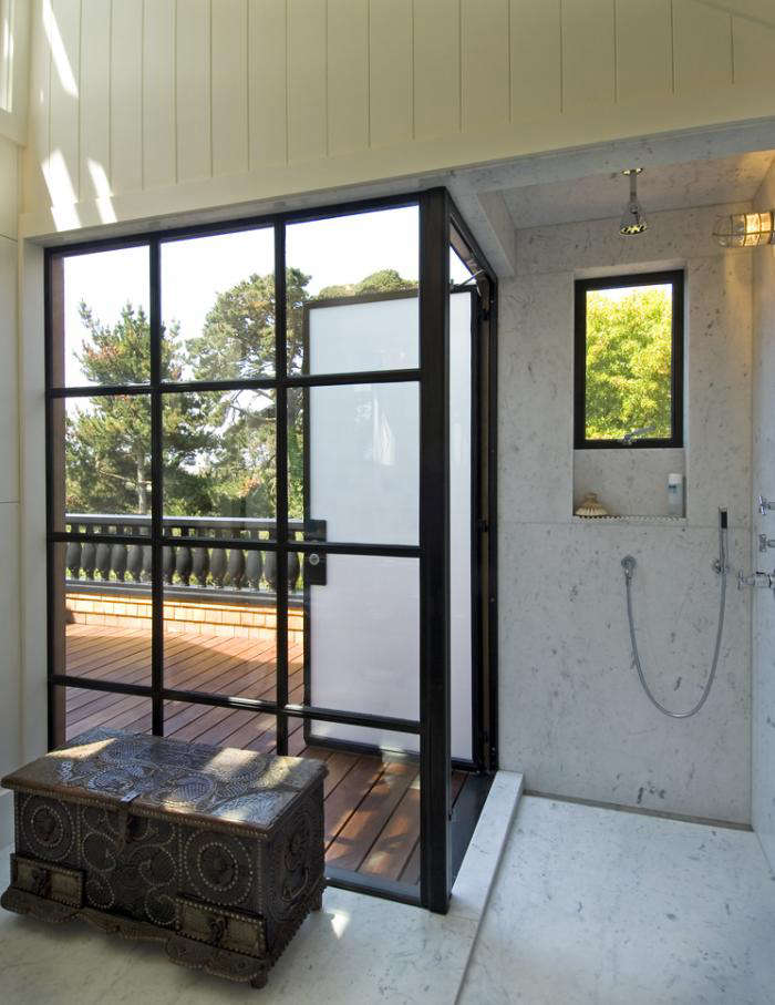 A marble-clad shower with an obscure-glass (frosted) door that opens onto a wooden roof deck and a small window looking onto the trees outside.