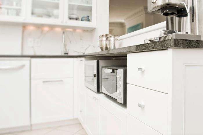 a microwave and a toaster oven tucked under a countertop ingeniously solves two 12