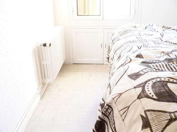 A tribal printed duvet in the otherwise white bedroom.