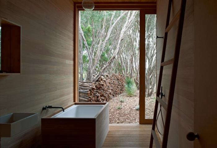 A ceramic soaking tub with a wood surround in the Melbourne home of architectsStephen O'Connor and Annick Houle.Photography by Earl Carter, courtesy ofO'Connor and Houle and featured inSlow House: A Serene Cabin in the Woods.