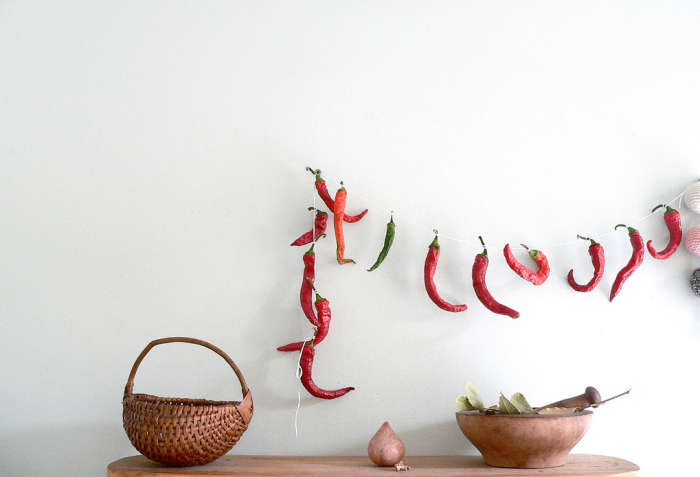 Dried chili peppers are threaded for ornamentation and for eating later.
