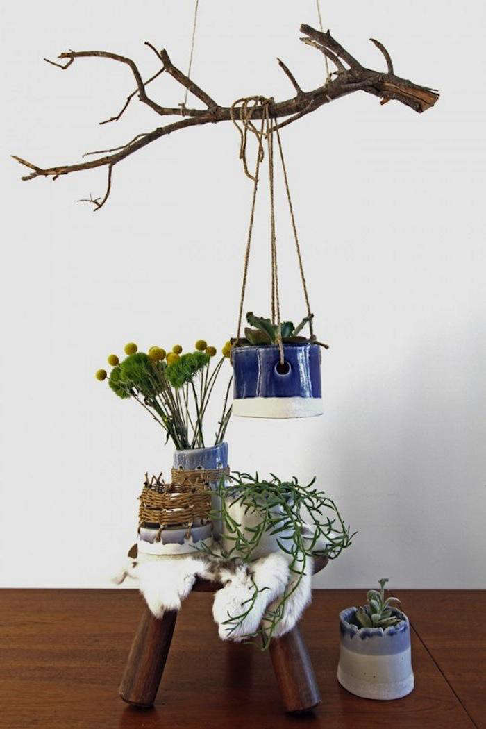 The New Rusticity 11 DIY Ways to Use Branches Indoors Particularly sturdy branches can serve as a hanger for planters, as seen in Rustic Planters from a British Potter in LA.